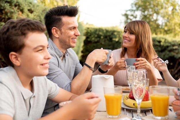 Famiglia che pranza insieme all'aperto
