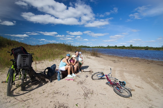Family having a rest on a river coast with their bikes around