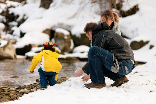 Family having winter walk at river