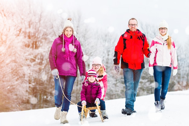 Family having winter walk in snow with sled