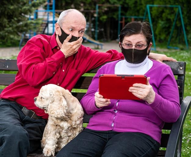 家族、ヘルスケア、テクノロジーのコンセプト。公園の屋外でタブレットpcを使用して顔の保護医療マスクの年配のカップル