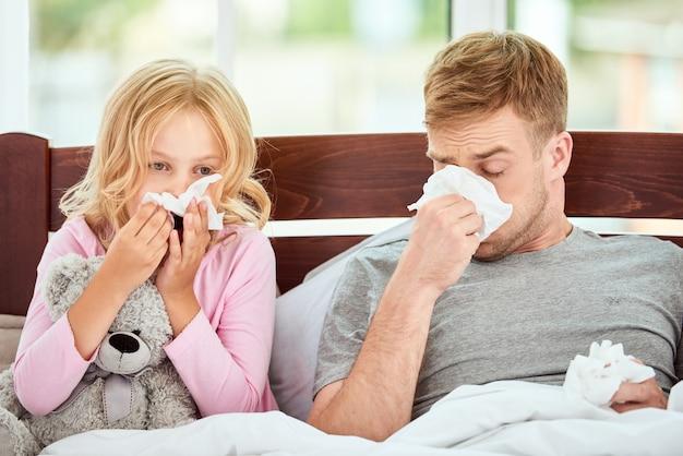 가족 건강 젊은 아버지와 그의 딸은 독감이나 감기와 콧물로 고통 받고 있습니다