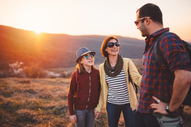 Family hiking and having fun on mountain during sunset