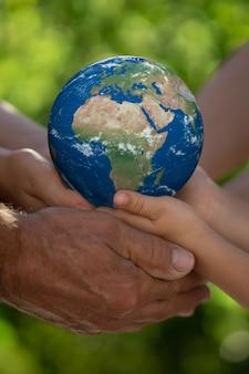 Семья, держащая в руках планету 3d. земляная перчатка. спасите нашу планету