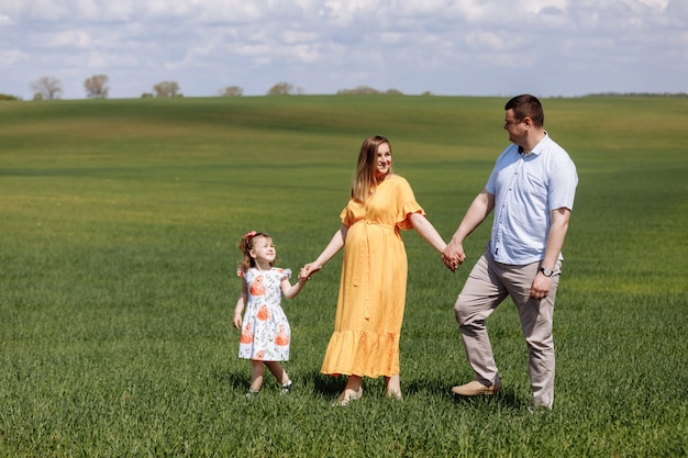 Семья, держась за руки, гуляет по полю