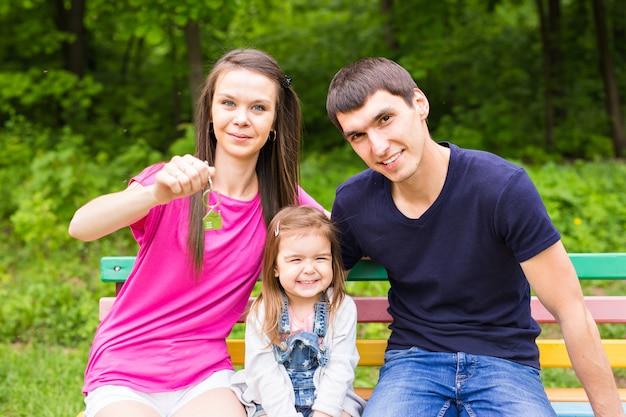 Семья держит ключи и улыбается на открытом воздухе