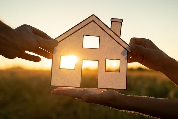 Семья держит бумажный домик на закате, солнце светит через окно, рука держит бумажный вырез с символами дома ...
