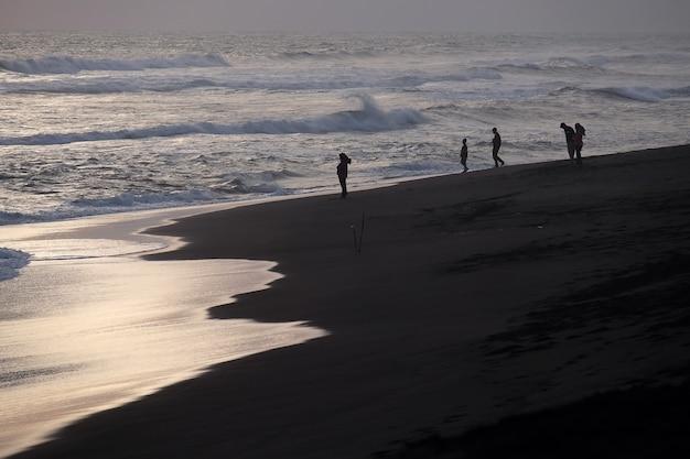 Семейный отдых на пляже во время заката в летнее время