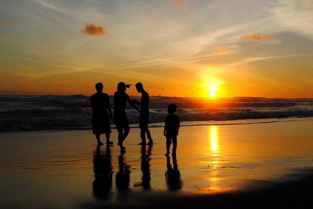 Семейный отдых на пляже во время заката