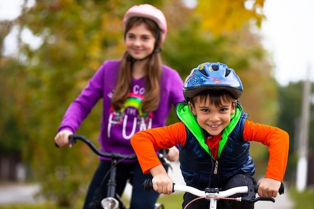 Семейный отдых. брат и сестра в парке. мальчик на велосипеде один.