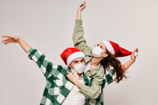 家族の休日のクリスマスと楽しい医療マスクお正月の帽子。