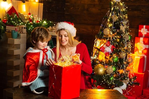 家族の休日。自宅で居心地の良い夜。ママと子供はクリスマスイブに一緒に遊ぼう。幸せな家族。楽しんでいる母と小さな子供男の子息子フレンドリーな家族。家で楽しんでいる家族のクリスマスツリー。