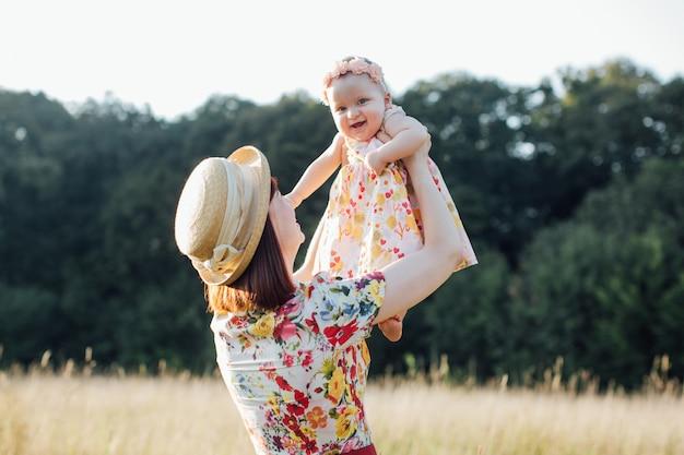 夏の日の家族の休日。美しいフィールドと木の背景に小さな娘とうれしそうな母。牧草地で遊ぶ美しい女性とかわいい赤ちゃん。
