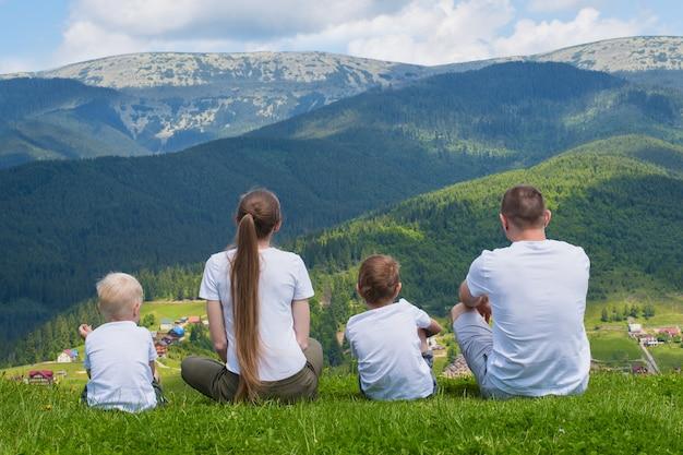 가족 휴가. 부모님과 두 아들은 산의 전망을 감상합니다. 다시보기. 화창한 여름날