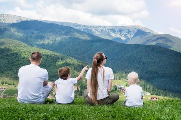 Семейный отдых. родители и двое сыновей восхищаются видом на горы. вид сзади. солнечный летний день