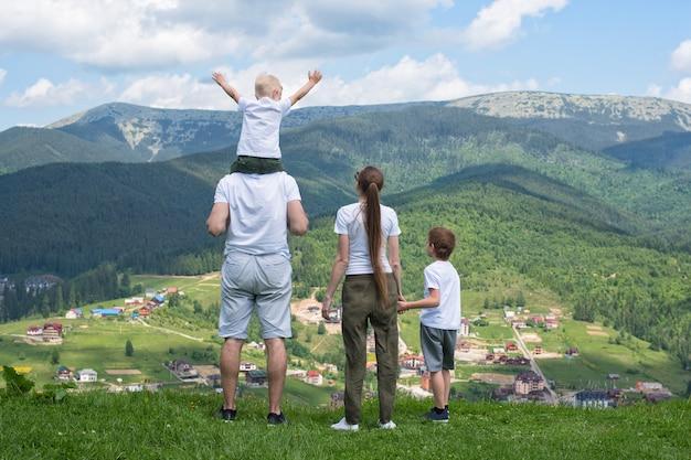 Семейный отдых. родители и двое сыновей восхищаются видом на долину. горы на расстоянии. вид сзади