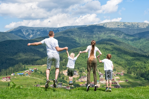 Family holiday. parents with children jump on mountains. back view.