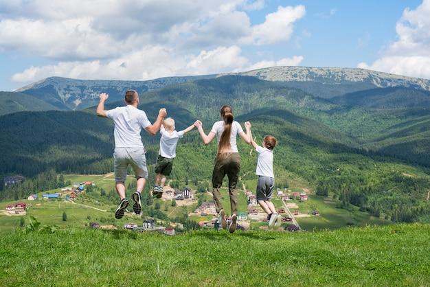 Семейный отдых. родители с детьми прыгают на фоне гор. вид сзади.