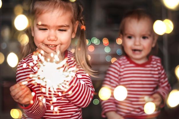 自宅での家族の休日。 2人の幸せな子供、幼児の男の子と燃える線香花火を持って幸せそうに笑うかわいい女の子