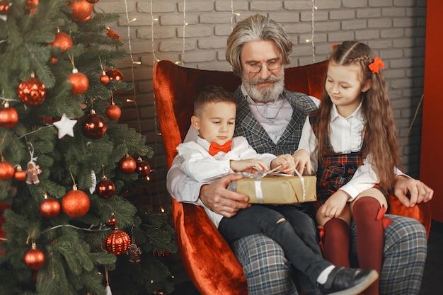 가족, 휴일, 세대, 크리스마스 및 사람들 개념. 크리스마스를 위해 꾸며진 방에있는 아이들.