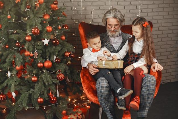 Concetto di famiglia, vacanze, generazione, natale e persone. bambini in una stanza addobbata per natale