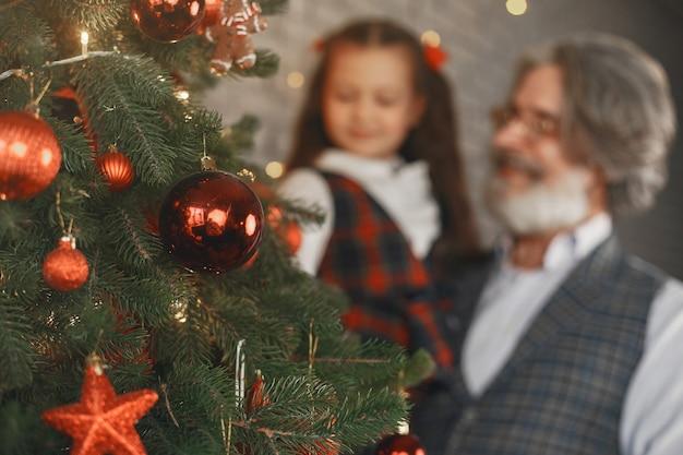 Concetto di famiglia, vacanze, generazione, natale e persone. camera decorata per natale