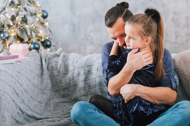 家族の家のクリスマスのお祝い。幸せな父は彼のかわいい小さな娘を抱き締めて、笑っています。スペースをコピーします。