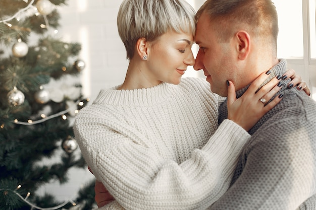 Family at home. couple near christmas decorations. woman in a gray sweater.