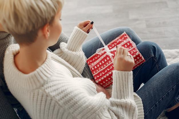 Famiglia a casa. coppia vicino a decorazioni natalizie. donna in un maglione grigio.