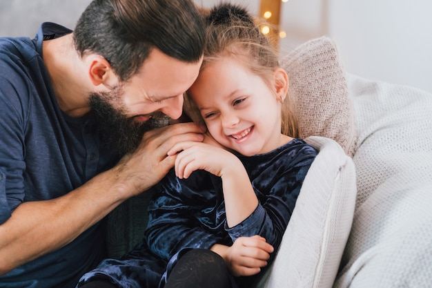 家族の家の楽しみ。冗談を言っている愛情のある父、笑っている彼のかわいい小さな娘の女の子。