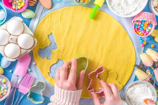 家族の自家製の休日イースターペストリーのコンセプト。ママと娘の子の手でイースターベーキングの背景
