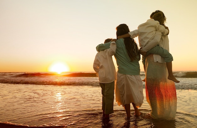Family hugging each other while standing on the beach surrounded by the sea during the sunset