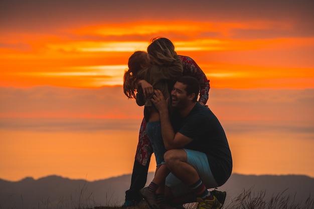 日没時に山の頂上で抱き締める家族