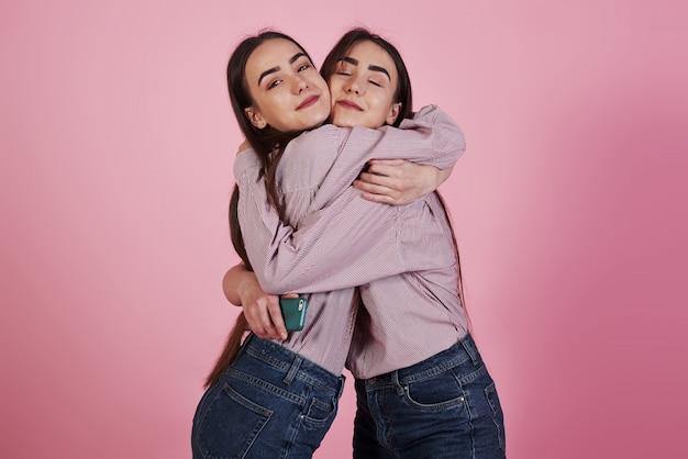家族が2人の姉妹を同じ服で抱きしめる