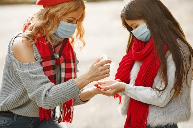 가을 공원에서 가족입니다. 코로나 바이러스 테마. 딸과 어머니. 사람들은 항균제를 사용합니다.