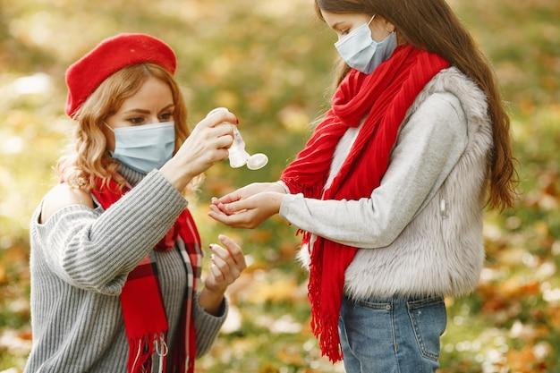 秋の公園の家族。コロナウイルスのテーマ。娘と母。人々は防腐剤を使用します。