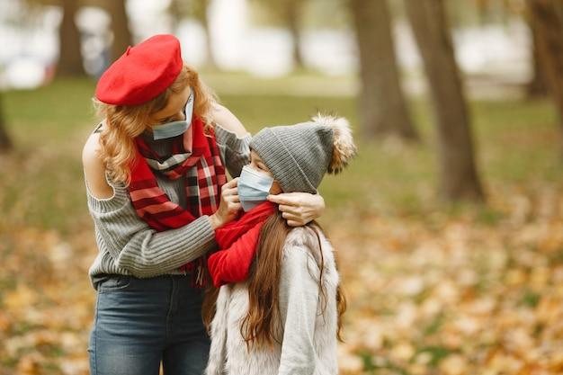 가을 공원에서 가족입니다. 코로나 바이러스 테마. 딸과 어머니.