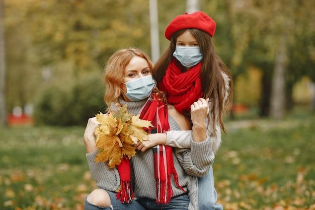 秋の公園の家族。コロナウイルスのテーマ。娘と母。