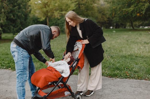 秋の公園の家族。黒のジャケットを着た男。両親とかわいい女の子。