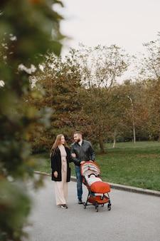 Семья в осеннем парке. мужчина в черной куртке. милая маленькая девочка с родителями.