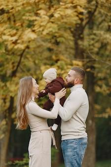 Семья в осеннем парке. мужчина в коричневом свитере. милая маленькая девочка с родителями.