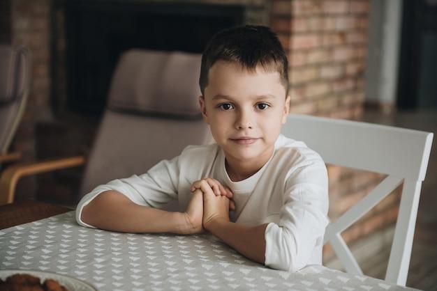 Семья в большом доме. стиль жизни домашний уют. дети дома. прекрасная кухня. портрет мальчика за столом. в ожидании ужина. детская диета. детская еда.