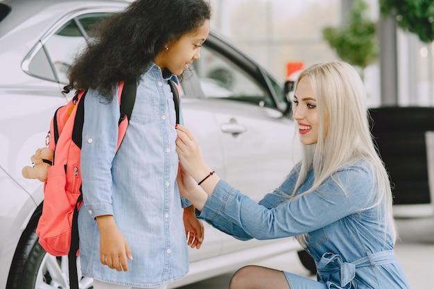 자동차 살롱에서 가족. 차를 사는 여자. mther와 작은 아프리카 소녀.