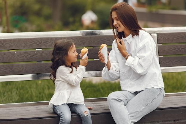 도시의 가족. 어린 소녀는 아이스크림을 먹는다. 벤치에 앉아 딸과 어머니입니다.