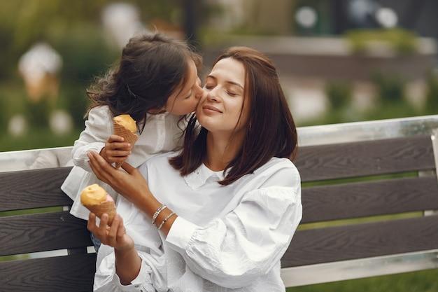 Семья в городе. маленькая девочка ест мороженое. мать с дочерью, сидя на скамейке.