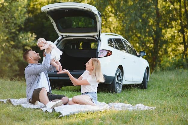 숲에서 가족입니다. 차에 의해 사람들입니다. 일몰 배경입니다.