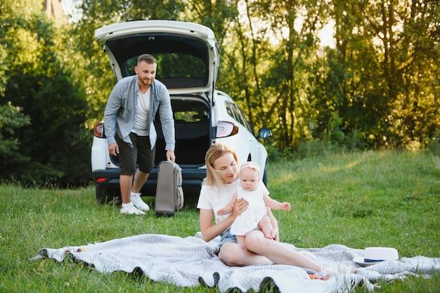 Семья в лесу. люди у машины. фон заката.