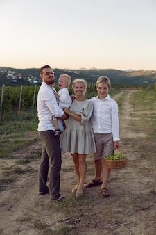 夏の日没時のブドウ畑の家族