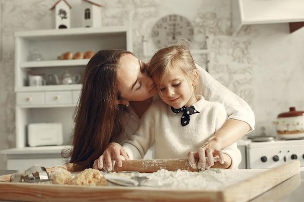 キッチンの家族。小さな娘を持つ美しい母親。