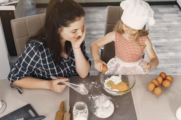 Семья на кухне готовит тесто для печенья